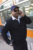 stock photo of bus driver  - African American bus driver answering phone call while standing by a bus - JPG