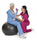 Female health care professional assisting female senior citizen with exercise technique.