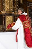 Catholic priest putting a covered chalice back into the tabernacle of a medieval church with 17th ce