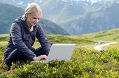Young Blonde Woman Sits With Laptop In Alpine Meadow