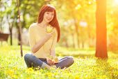 Happy woman eating fruits in the park