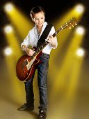 Boy Playing On Electric Guitar On The Stage