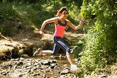 pic of leaping  - Sporty young woman leaping over a stream in a forest on a run - JPG
