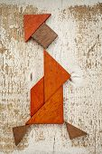 abstract figure of a walking woman built from seven tangram wooden pieces, a traditional Chinese puzzle game; rough white painted barn wood background