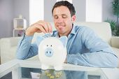 Good looking casual man putting coin in piggy bank and looking down in bright living room