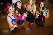 Happy gorgeous women holding flutes of champagne having hen party in a classy bar