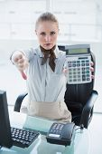 Blonde stern businesswoman showing calculator and thumb down in bright office