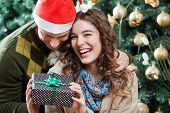 Cheerful young couple with present against Christmas tree in store