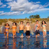 Teen surfers boys and girls group running happy to the beach splashing water