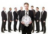 Business Manager with a clock in front of his team