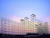 stock photo of scaffolding  - Complex scaffolding setup for a stage for an outdoor concert seen at sunset