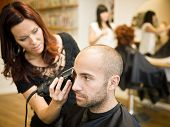 image of electric trimmer  - Adult man being shaved at the hair salon - JPG