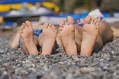 Children's feet  on grass. Family picnic on the beach