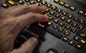 Hand On Illuminated Industrial Qwerty Keyboard. Selective Focus