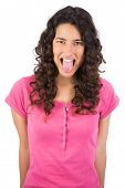 Disgusted long haired brunette on white background sticking her tongue out