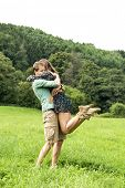 Woman, affectionately jumping into her boyfriends arms in the middle of a meadow