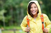 Rain woman hiking happy in forest. Female hiker portrait standing with backpack joyful on rainy day