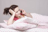 Young Girl Talking On Phone Lying In Bed