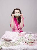 Girl Sitting On The Bed Rejoices Money