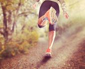 an athletic pair of legs running on a path during sunrise or sunset - healthy lifestyle concept