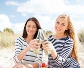 summer, holidays, vacation, happy people concept - smiling girlfriends with bottles of beer or non-a