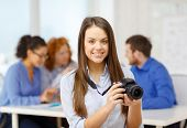 business, office and startup concept - smiling female photographer with photocamera in office with t