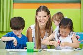 Happy child care worker with children drawing in a kindergarten