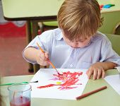 Child painting with brush and paper in a kindergarten