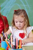 Girl drawing with many colorful crayons in a kindergarten