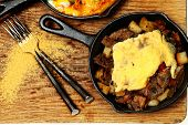 Texas Skillet Breakfast with Steak, Potato and Egg on Table