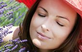 Young Woman With Hat Sniffs Lavender Flowers