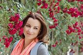 Beautiful Woman In Garden Under Red Roses Bower