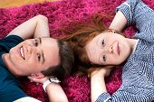 Two Teenagers Lying On Carpet