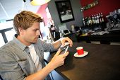 Young man in coffee shop websurfing on internet