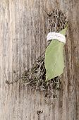 stock photo of covenant  - dried thyme covenant and bay leaf on rustic wood - JPG
