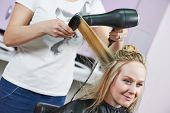 foto of beauty parlour  - hairdresser drying hair with blow dryer of woman client at beauty parlour after highlighting - JPG