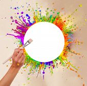 Colored paint splashes in round shape with free space for text in center. Woman hand holding paintbr