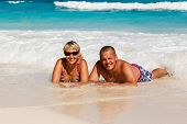 Young romantic couple laying on sandy beach
