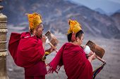 THIKSEY, INDIA - SEPTEMBER 4, 2011: Two Tibetan Buddhist monks blowing conches during morning pooja,