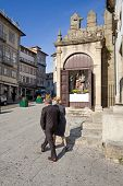 Guimaraes, Portugal - March 25, 2013: Locals pass by one of the Stations of the Cross especially ope