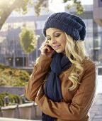 Pretty woman talking on mobilephone at autumn outdoors, wearing hat and scarf.