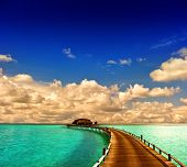 Tropical Sunset Seascape. Overwater Bungalow With Jetty