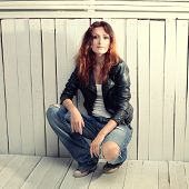 stock photo of straight jacket  - Beautiful young woman in jeans and black leather jacket sitting against grunge wood wall - JPG