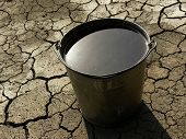 bucket full of water on dry soil background