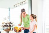 Mother giving child fresh fruits for healthy living in home kitchen