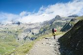 VILLE DES GLACIERS, FRANCE - AUGUST 27: Hiker walking towards Glacier Needles. The region is a stage
