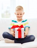 leisure, childhood, holidays and home concept - smiling little holding gift box with red bow and sit