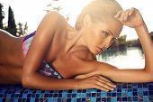Beautiful Girl With Blond Hair In Bikini Posing Beside A Swimming Pool