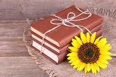 Books and sunflower on wooden table on wooden wall background