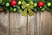 Fir branch and Christmas balls on wooden background